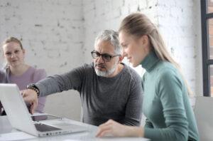 Erfahrener Projektmitarbeiter erklärt am Laptop
