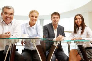 Teilnehmer eines Projektmanagement-Teams sitzen an einem Tisch